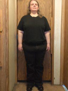 front view of Sarah standing in front of a door